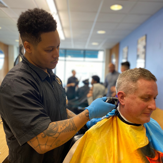 A student at Champions Barbering Institute Cuts Hair