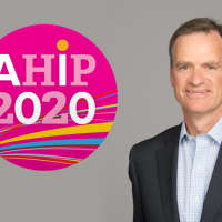 Mark Ganz standing next to the AHIP logo