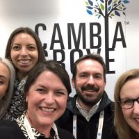 A group of people standing in front of the Cambia Grove logo