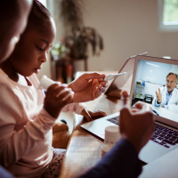 A father and daughter have a telehealth appointment with a doctor
